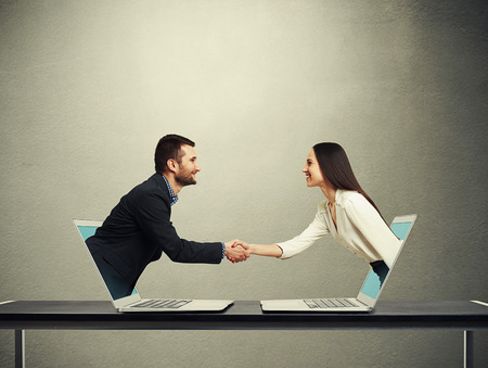 Foto de smiley businessman and businesswoman come out from laptop, shaking hands and looking at each other over dark grey background - Imagen libre de derechos