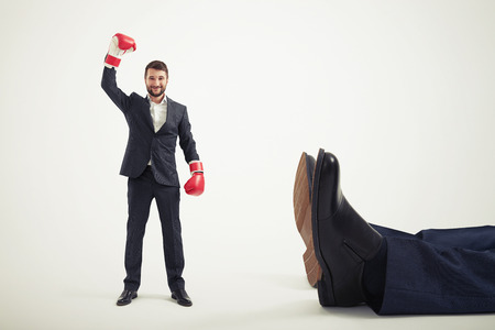 smiley winner businessman in red boxing gloves standing near big lying mans legs over light grey background