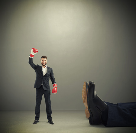 Photo pour happy winner businessman in red boxing gloves standing near big lying mans legs over dark grey background - image libre de droit