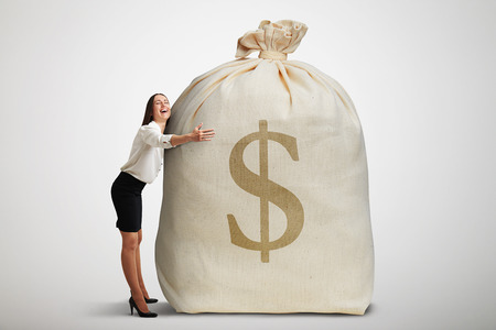 happy woman embracing big bag with money and smiling over light grey background
