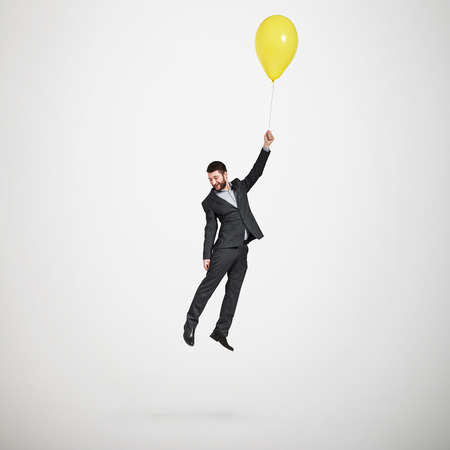 Photo pour laughing man flying with yellow balloon and looking down over light grey background - image libre de droit