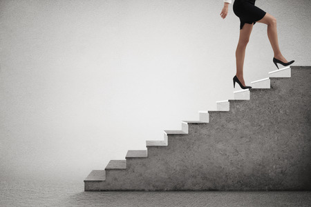 woman in formal wear walking up stairs over light grey background