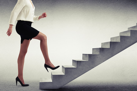 businesswoman in formal wear walking up stairs over light grey background