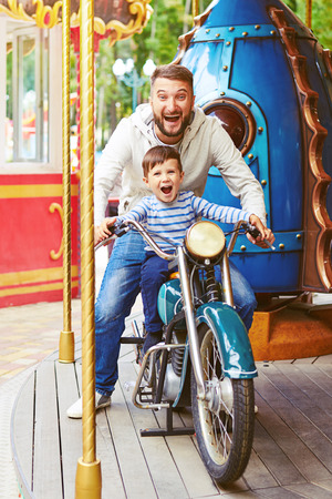 excited man with little boy having fun on motorcycle on merry-go-round