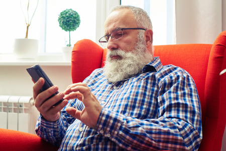 serious senior man in glasses sitting on the chair and using his smartphone at home