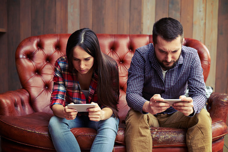 Photo pour concept photo of smartphone addiction. young woman and man sitting on the sofa with smartphone and do not looking at each other - image libre de droit