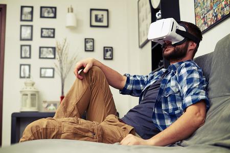 Photo pour Young Caucasian man resting on comfortable sofa wearing VR headset glasses - image libre de droit