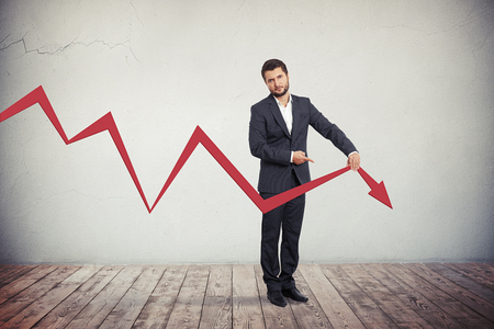 Foto de Disappointed businessman pointing to red graph arrow down. - Imagen libre de derechos