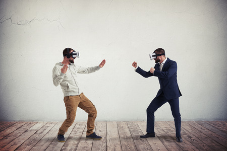 Photo pour Two men, one in casual clothes, another in dark business suit, are wearing virtual reality glasses and combating in virtual reality in white room with wooden floor - image libre de droit