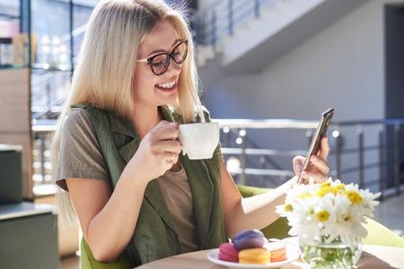 Foto de Beautiful woman using mobile phone at cafe - Imagen libre de derechos