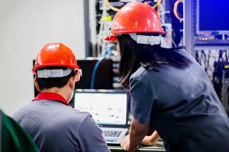 Foto de A portrait of an industrial man and woman engineer with laptop in control room of factory. Engineer Controller Observes Working of the System. In the Background People Working and Monitors Show Various Information. - Imagen libre de derechos