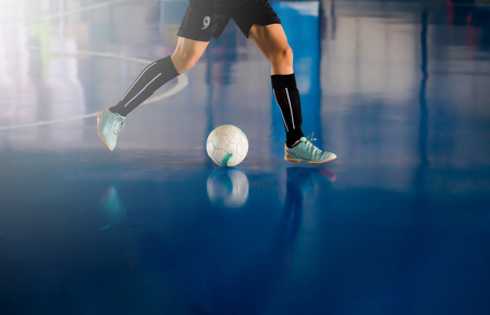 Futsal player trap and control the ball for shoot to goal. Soccer players fighting each other by kicking the ball. Indoor soccer sports hall. Football futsal player, ball, futsal floor. Sports background. Youth futsal league. Indoor football players with