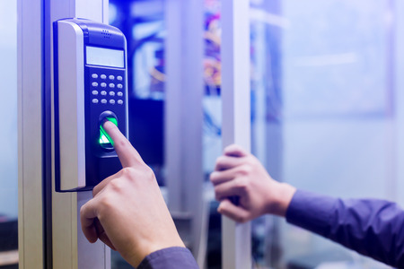 Photo pour Staff push down electronic control machine with finger scan to access the door of control room or data center. The concept of data security or data access control. - image libre de droit