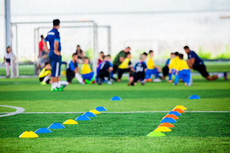 Foto de Cone markers is soccer training equipment on green artificial turf with blurry kid players training background. Material for trainning class of football academy - Imagen libre de derechos