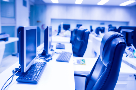 composite image of computer in office or training room. the computer is on the table in a bright interior. white desk and black revolving chair with computer pc and mouse in office.