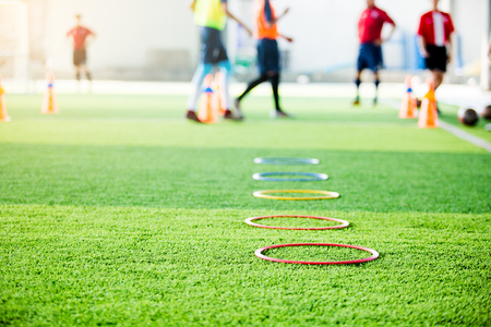 Photo pour selective focus to ring ladder marker and cone are soccer training equipment on green artificial turf with blurry kid players training background. material for training class of football academy. - image libre de droit