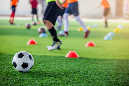 Soccer ball on green artificial turf with blurry of maker cones and player training. Soccer academy