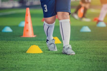 Foto de kid soccer player Jogging and jump between cone markers on green artificial turf for soccer training. Football or Soccer Academy. - Imagen libre de derechos