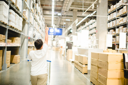 Asian boy is pointing their fingers to choose products and pushing a shopping cart in warehouse for shopping, large warehouse, warehouse interior, selective focus and blurry background.
