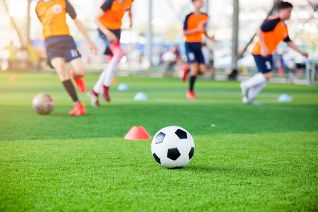 Photo for soccer ball and marker cones on green artificial turf with blurry soccer team training, blurry kid soccer player jogging between marker cones and control ball with soccer equipment in soccer academy. - Royalty Free Image