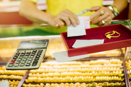 Photo pour the calculator to calculate the purchase of gold jewelry with sale blurry staff holding  ticket in the gold shop. - image libre de droit