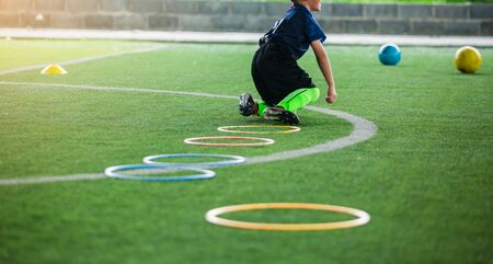 Photo for selective focus to kid soccer player Jogging and jump at ring ladder marker on green artificial turf. equipment for training class of football academy. kid football player falling while practicing. - Royalty Free Image