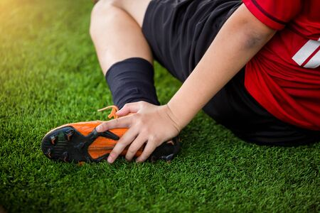 Photo pour footballer is sitting and catch the ankle of the feet because of pain, soccer player was injured in the foot with pain during competition or practice. - image libre de droit