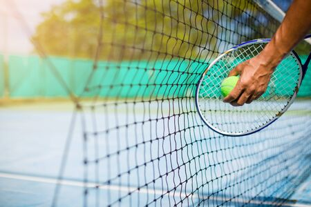 Foto per Selective focus to net with blurry tennis ball in hand and racket in court under sunlight. Tennis game. Sport, recreation concept - Immagine Royalty Free