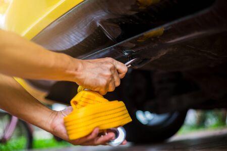 Photo pour Hands of man holding yellow car towing strap with yellow car. Yellow car towing. towing rope. - image libre de droit