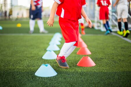 Foto de Kid soccer player Jogging and jump between red and blue cone markers on green artificial turf for soccer training. Football or soccer academy. - Imagen libre de derechos