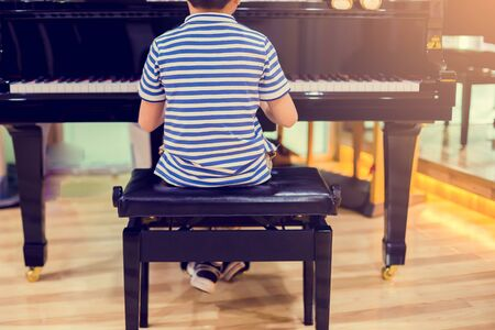 View from the back of boy play piano on stage. There are musical instrument for concert or learning music.