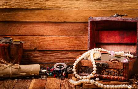 Open wooden treasure chest with valuables on wooden background