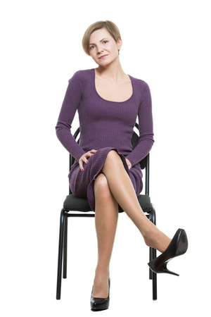 woman sits a chair. pose showing sexual desire. flirting. legs crossed, shoe drops. flexing. Isolated on white background. body language
