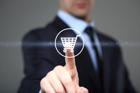 Foto de Online shopping  concept with businessman touching virtual shopping cart.  business, technology, internet and networking concept - Imagen libre de derechos