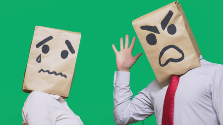 Photo for The concept of emotions and gestures. Two people in paper bags with smileys. Aggressive smiley swears. The second crying sad. - Royalty Free Image