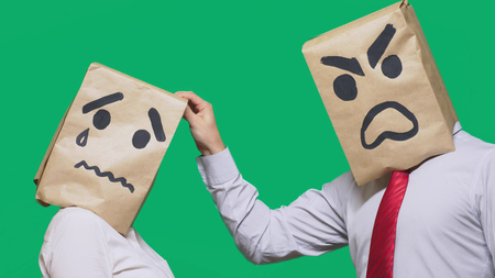 Photo pour The concept of emotions and gestures. Two people in paper bags with smileys. Aggressive smiley swears. The second crying sad. - image libre de droit