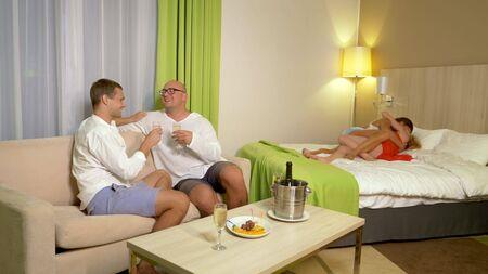 Photo pour LGBT concept. LGBT couples kissing at a house party. - image libre de droit
