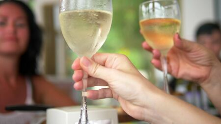 Photo pour close-up. people clink glasses of wine at a table at a friendly or family dinner - image libre de droit