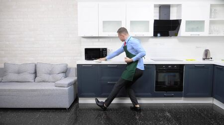 Photo pour handsome man in an apron and tie. cleans up the kitchen in the apartment - image libre de droit