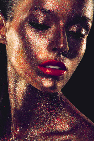 Beautyful girl with gold glitter on her face and red lips