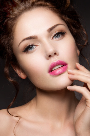 Close-up portrait of beautiful woman with bright make-up and pink lips