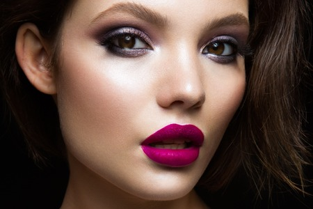 Beautiful young model with pink lips and dark makeap