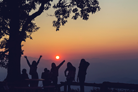 Happy peoples silhouetted with stunning sunset