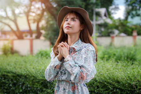 Asian woman believe in the prayer to God. Pretty girl make a wish motion on blurred park background.