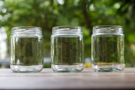Three empty round shape glass canisters on wooden desk with nature background