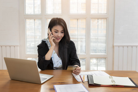 Photo pour Young asian woman holding credit card and using smart phone for purchase product on internet in home office. Online shopping concept. - image libre de droit
