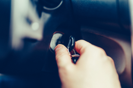 The driver of the man gets a car with a key. The hand inserts the key into the ignition and starts the car. Hand put the car key to the keyhole starting the car. Stylish Toned Photo