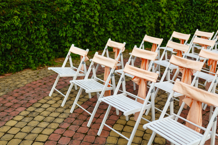 Foto de White wooden chairs decorated with orange bows and roses for holiday or anniversary ceremony in row outdoors on green grass background. Wedding and celebration - Imagen libre de derechos