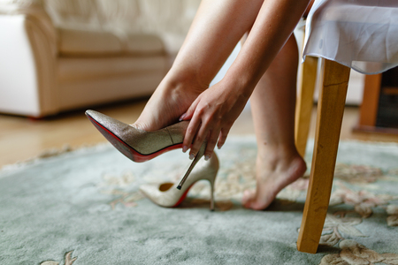 Foto de The girl tries on beautiful expensive high-heeled shoes in the bedroom or hotel. Bride's feet in wedding shoes, close-up, closed. - Imagen libre de derechos