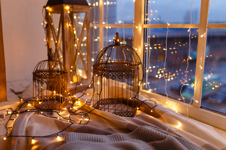 Foto de Cages for birds covered with garland with yellow lights. Cozy winter or autumn morning at home. Warm blanket, garland with lights Swedish concept hygge. - Imagen libre de derechos